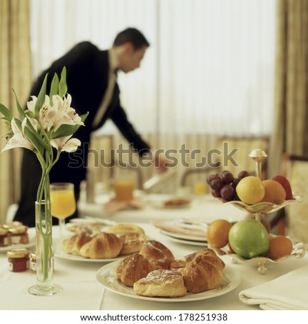 Big Hotel room service continental breakfast with waitress out of focus  - stock photo