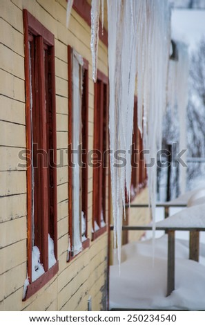 Big icicles hanging from the roof of house with wooden walls - traditional winter pattern for northern Russia (Murmank region) - stock photo