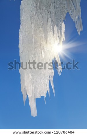 Big icicles with sun sparkles on blue sky background with copy space - stock photo