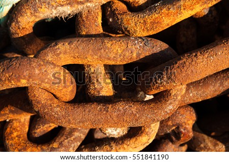 Big iron chains from an old ships anchor rusting by the harbor side close up