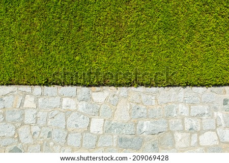 Big isolated natural fence around a house made of stone and nicely trimmed green belt - stock photo