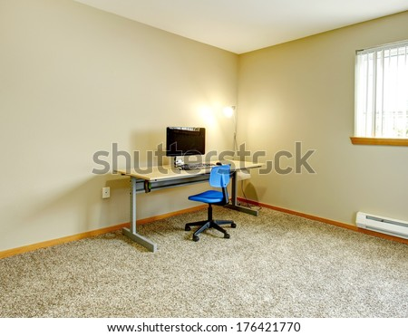 Big ivory office room with window and beige carpet floor. Furnished with small desk and computer - stock photo