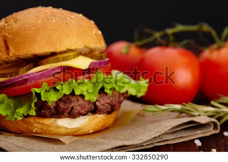 Big juicy beef burger on background tomatoes and herbs.