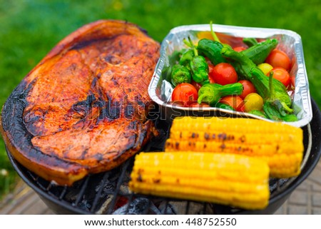 big juicy peace of pork, vegetables variety in metallic foil and corn grilling over the glowing coals on BBQ outdoors on green lawn - stock photo