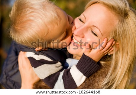 Big kiss for mom, cute young boy kissing his mother. - stock photo