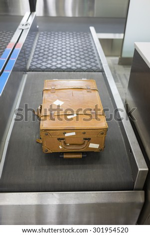 Big leather suitcase at check-in desk at airport - stock photo