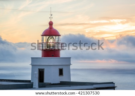 Big lighthouse building with red tower at beautiful sunset background. Ponta do Pargo, Madeira island, Portugal
