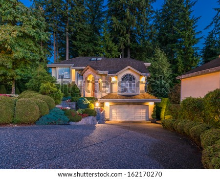 Big luxury house with triple garage at night, disk, sunset, sunrise time in suburbs of Vancouver, Canada. - stock photo