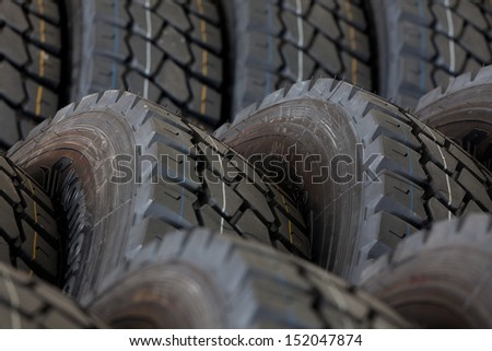 Big machines tires stack background. Industrial tires - stock photo