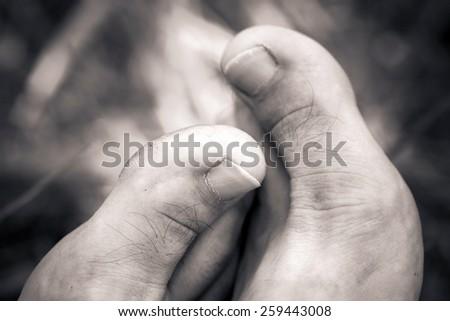 Big man barefoot close-up thumbs - stock photo