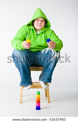 Big man in a green jacket with hood with toys - stock photo