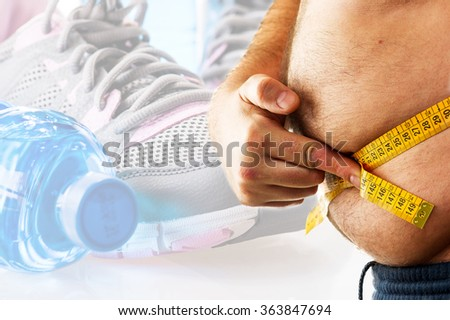 big man measuring his belly with a measuring tape and fitness background - stock photo