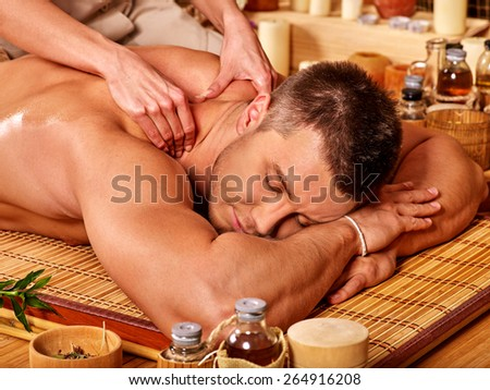 Big man with eyes closed getting massage . Female therapist. - stock photo
