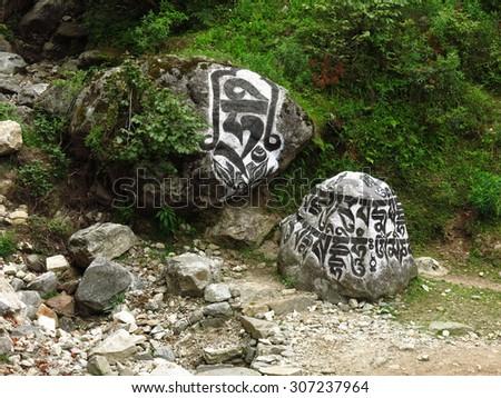 Big mani stones, boulder with engraved buddhist mantra - stock photo