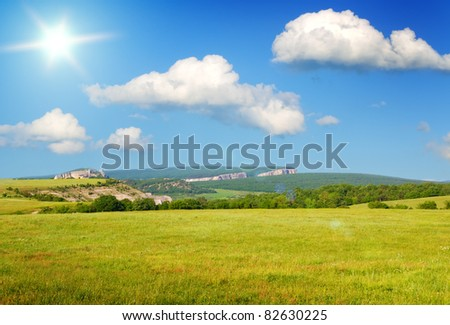 Big meadow on sunrise on mountain background. Composition of nature. - stock photo