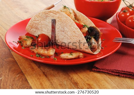 big mexican taco with tomatoes and mushroom, served with soup, fresh vegetables , on red crockery plates over wooden table with cutlery and napkin - stock photo