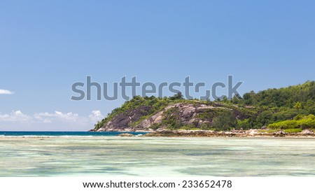 Big mountains covered with tropical forests and clear blue sea with waves at the large coral reef in the Seychelles, Africa - stock photo