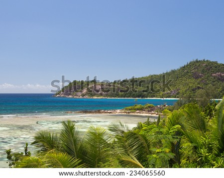 Big mountains covered with tropical forests and clear blue sea with waves in the coral reef in the Seychelles, Africa - stock photo