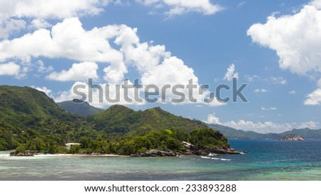 Big mountains covered with tropical forests and clear blue sea with waves in the Seychelles, Africa - stock photo