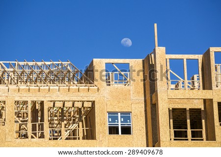 Big multifamily housing under construction against blue sky - stock photo