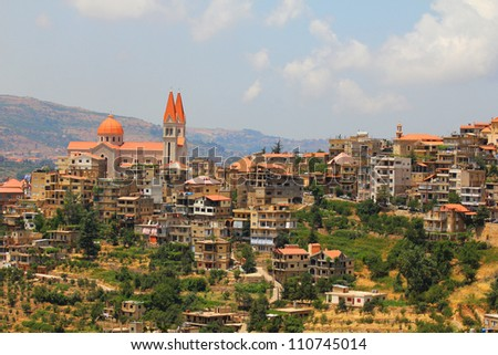Big number of buildings at the mountains with one big church rising high between them. - stock photo