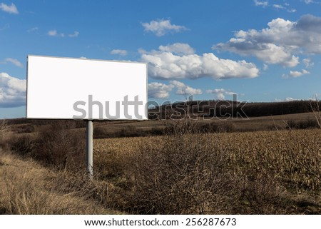 Big oblong billboard in fileds next to the road