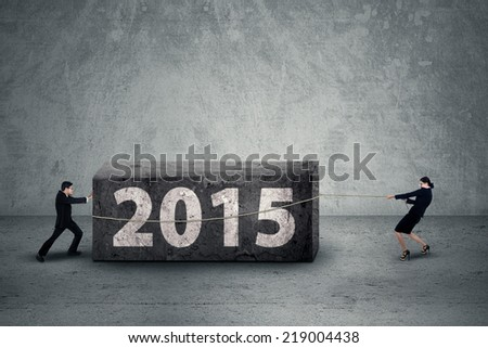 Big obstacle concept in 2015, businesspeople move a boulder with a text of 2015 - stock photo