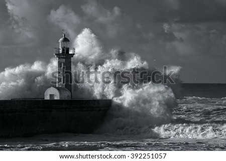 Big ocean stormy waves over old lighthouse of Douro mouth granite pier. Used infrared filter. Toned blue.