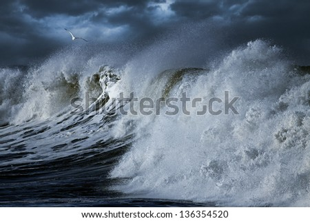 Big Ocean wave seeing splash and  spray made by wind in the Portuguese coast; enhanced sky - stock photo