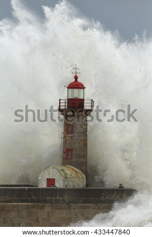 Big ocean waves against old lighthouse and pier in a stormy afternoon - stock photo