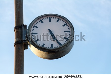 big old clock at a rusty pole against the blue sky with copy space - stock photo