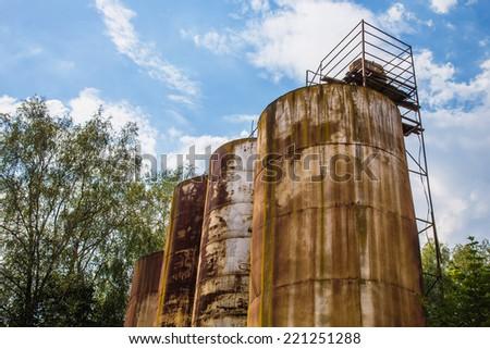 Big old deserted rusty tanks - stock photo