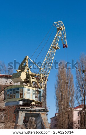 big old  port crane on blue sky background - stock photo