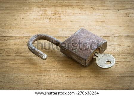 Big old rusty open padlock,focus at lock,padlock on wooden background - stock photo