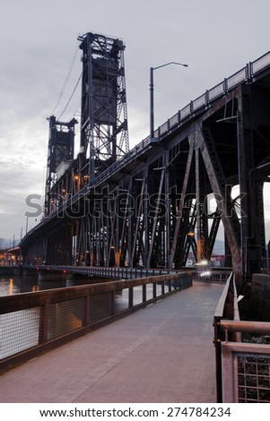 Big old two storey transport drawbridge with powerful triangular trusses with hiking and biking trails along first level of bridge railing fenced for compliance safety regulations with moving cyclist. - stock photo