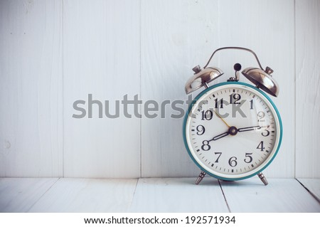 Big old vintage alarm clock with bells, painted white wooden background - stock photo