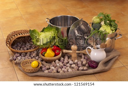 big pans and fresh vegetables stand on a floor in kitchen - stock photo