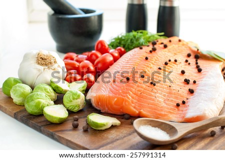 Big piece of fresh raw salmon/trout with vegetables and seasoning on wooden cutting board- ready to eat, ready to cook. Indoors close-up. - stock photo