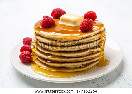 Big Pile of American  Pancakes with Raspberries, Melted Butter and Maple Syrup - stock photo