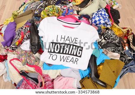 Big pile of clothes thrown on the ground with a t-shirt saying nothing to wear. Close up on a untidy cluttered wardrobe with colorful clothes and accessories, many clothes and nothing to wear. - stock photo