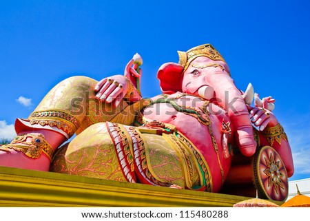 Big pink Ganesha in relaxed pose against blue sky background