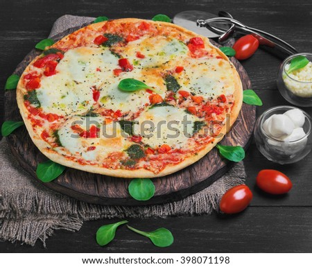 Big pizza with mozzarella into balls and shredded cheese, cherry tomatoes, lettuce on a cutting board round served on a dark black background wooden surface - stock photo