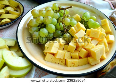 Big plate with green grapes and yellow cheese - stock photo