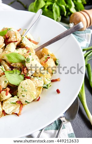 Big portion of potato salad from boiled young potatoes with yoghurt and mayonnaise dressing, roasted bacon, sliced green onions and basil leaves in white plate. Fork, spoon and bunch of basil near it.