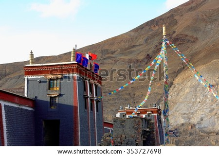 Big prayer flag pole at the eastern entrance to the South Seat of Sakya-Grey Soil monastery. Dhvajas and buddhist-chinese flags on rooftop. Sakya-Shigatse prefecture-Tibet. - stock photo