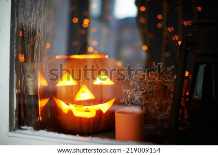 Big pumpkin with burning candle inside in a window - stock photo