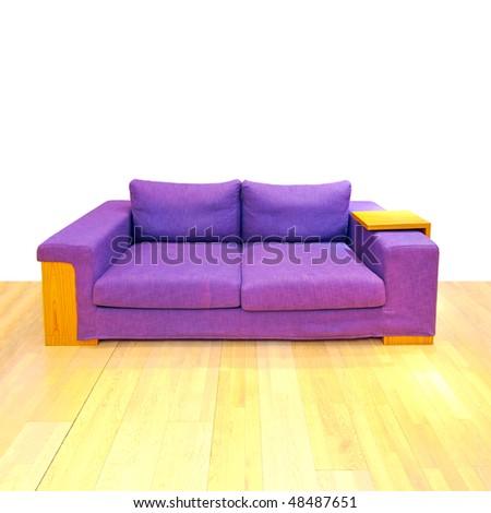 Big purple sofa in living room with hardwood floor - stock photo