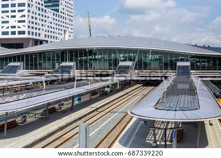 Big railway station with glass roofs, platforms and modern buildings. Utrecht, The Netherlands, July 2017