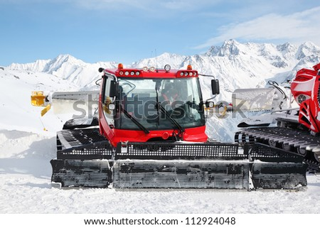 Big red machines for skiing slope preparations in Austrian Alps at day. - stock photo
