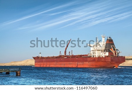 Big red oil tanker passes through the Suez Canal. Egypt - stock photo